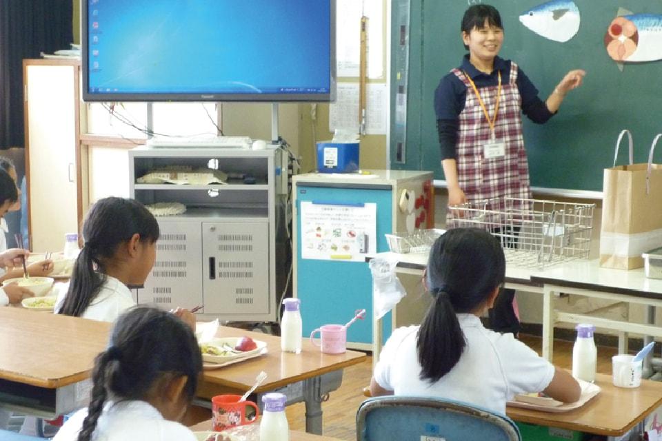 写真:女性が教育実習で黒板の前に立って生徒に説明をしています。