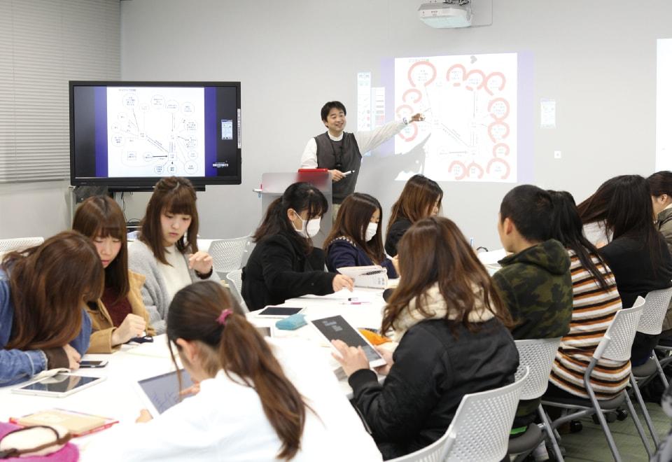 写真:社会福祉について授業を行う教員と、タブレット等を使用しながら講義を受けている学生たち