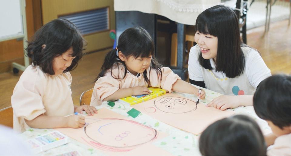 写真:幼稚園の実習で児童のお絵かきを見る女子学生