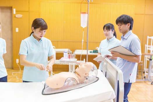 写真:医療的ケアの様子。模型で胃瘻の使い方を実践する学生