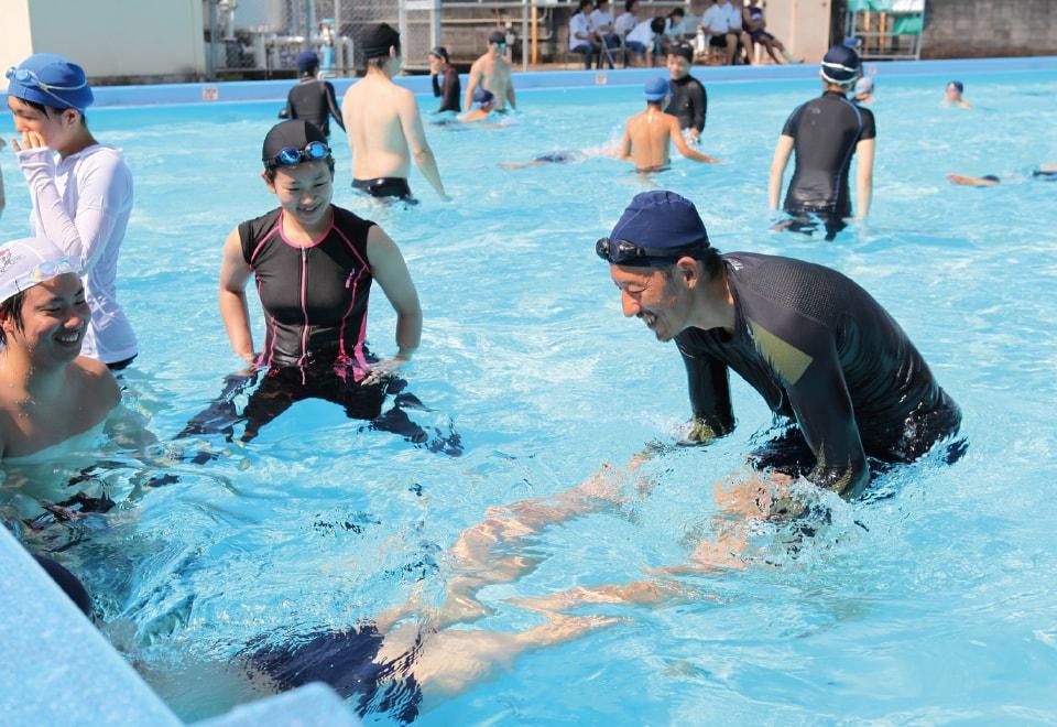 写真:体育科教育法。小学校でプールの中で泳ぎの指導をしている様子