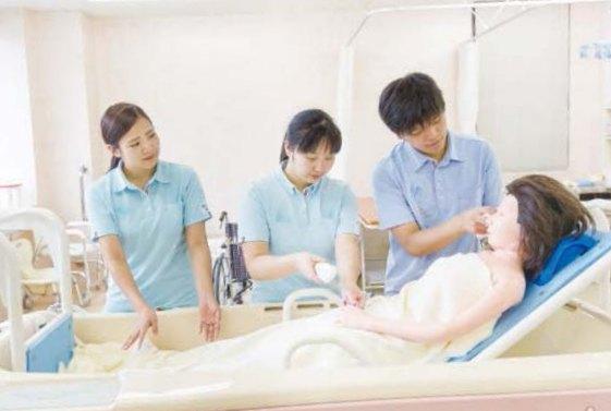 写真:生活支援技術B。車いすから介護用のベッドに移動させる介護の様子