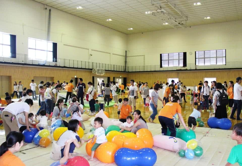 写真:体育館に設置された様々な手作りの遊具で遊ぶ大勢の親子と対応する学生たち
