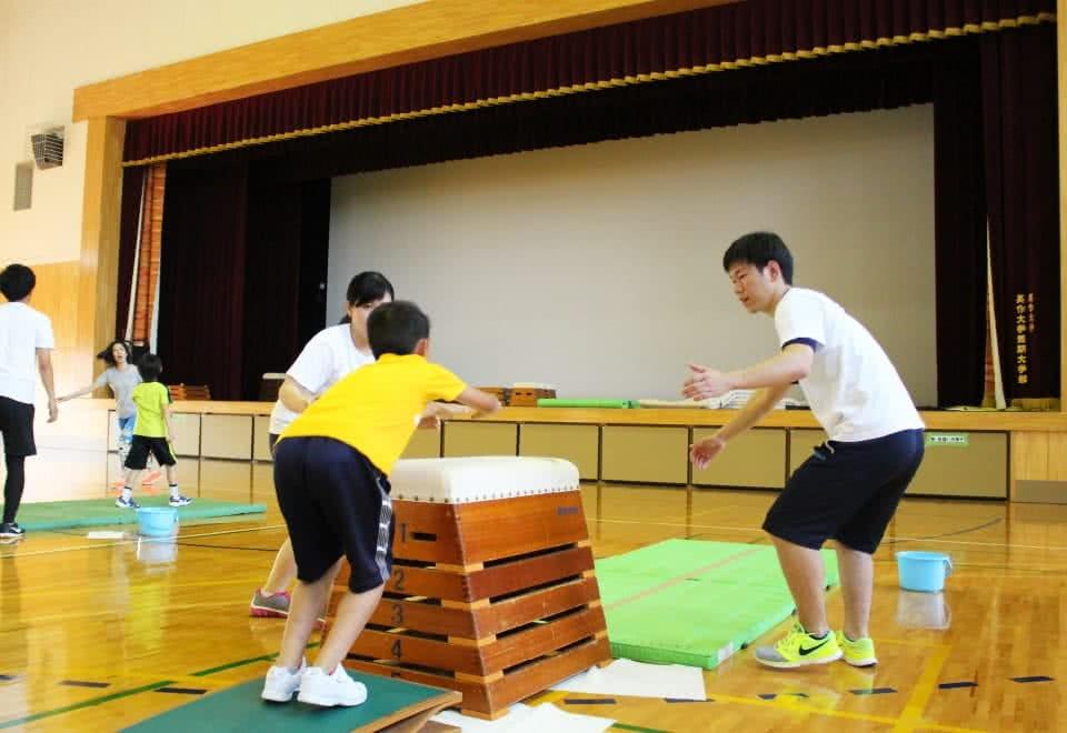 写真:体操教室で跳び箱を飛ぶ小学生と、それをサポートする学生