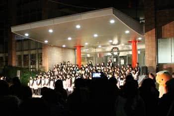 写真:正面玄関の階段に並んで歌を歌う大勢の学生