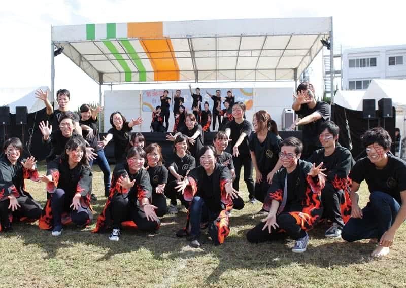 写真:野外ステージの前で両手を広げたポーズで写真に収まる岡山県人会のメンバーたち