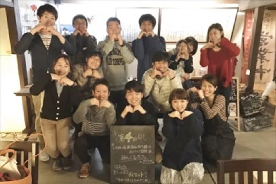写真:みんくるカフェの会場で「M」のポーズを手で作る、学生と教員と参加者