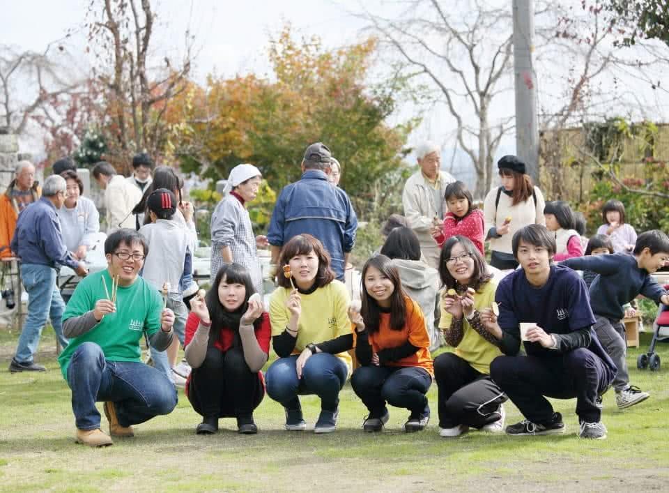 写真:公園で手に食べ物をもってしゃがんで写真に収まる学生たち