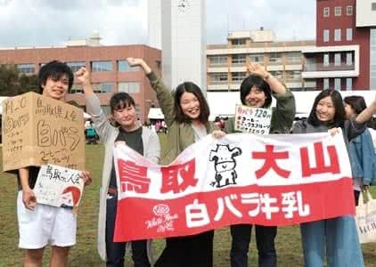 鳥取大山 白バラ牛乳と書かれた垂れ幕を持ち腕を上げる4人の鳥取県人会の女子メンバーと、鳥取県人会 白バラコーヒーと書かれたダンボールをかぶった男子メンバー