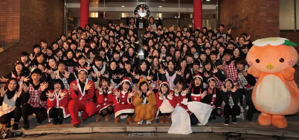 写真:イルミネーションて等式の集合写真に収まる生徒たちとみまっぱちゃん
