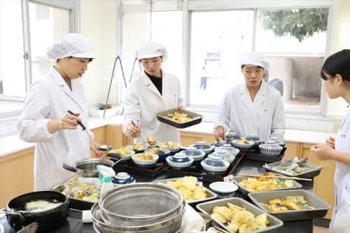 写真:天ぷらを調理する4名の女子学生