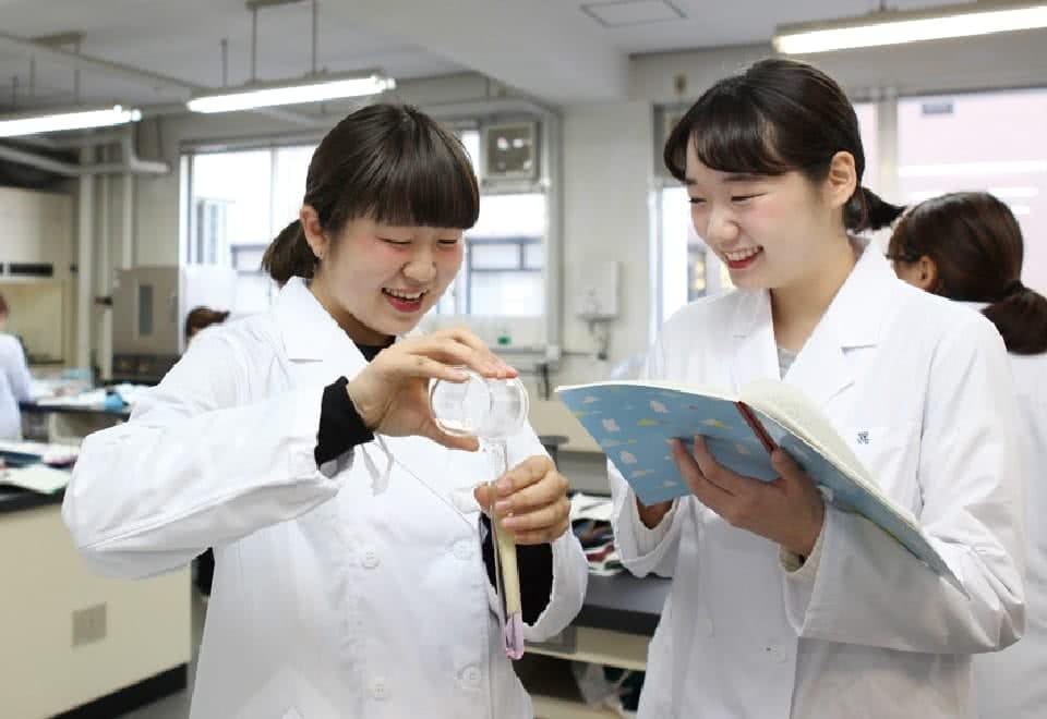 写真:授業を受ける白衣のDさんと友達