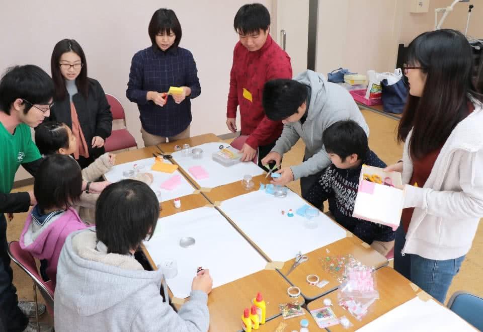 写真:手作りのスノードームを作る子どもたちとトライアングルサークルの学生たち