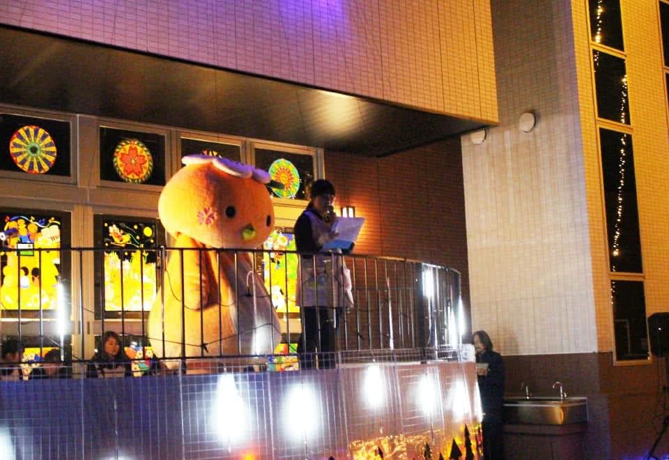 写真:サークルコモンズの半円ステージにいるみまっぱちゃんとマイクを持った女子学生。