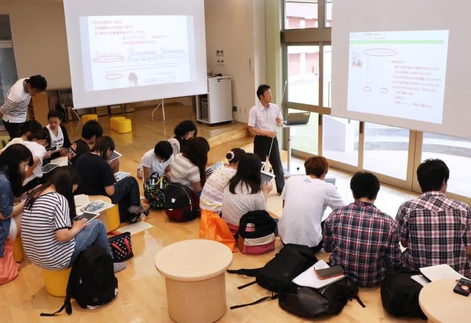 写真:サークルコモンズのステージ中央でプロジェクターを使った授業を行っている教員と、それを聞いている学生たち。