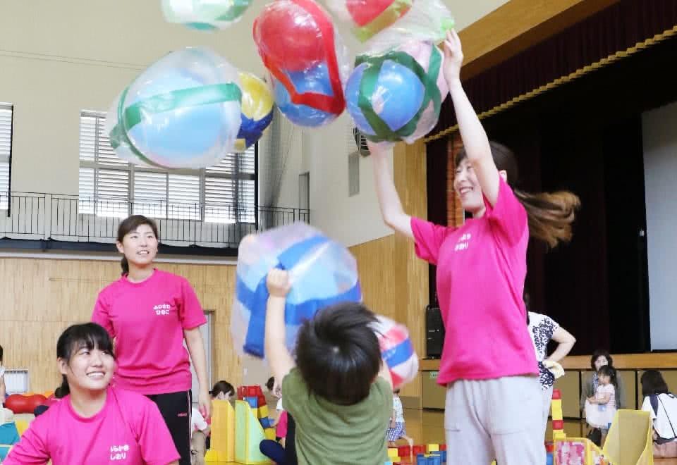 写真:手作りの遊具で遊ぶ子どもと学生