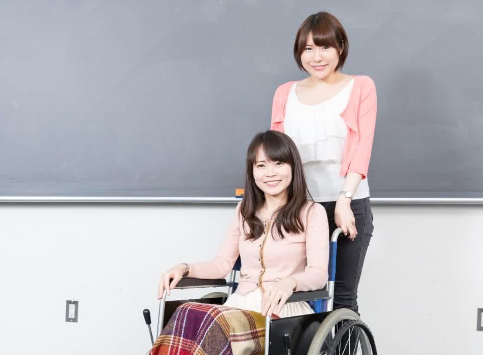 写真:黒板の前で車椅子に座っている女子学生と、その車椅子をもつ女子学生。