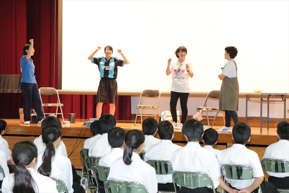 写真:ガッツポーズなどの手振り身振りを交えながら、中学生に劇を披露する4名の女子学生