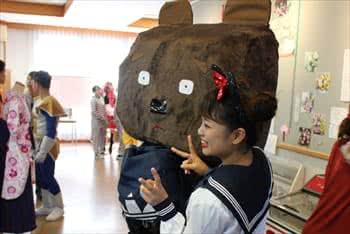写真:巨大な熊の被り物をしている学生と制服を着ている学生