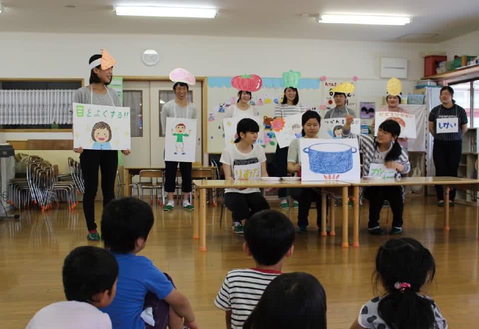写真:食べ物のお面をつけた学生達が紙芝居等で幼稚園児に食についてお話をしている様子