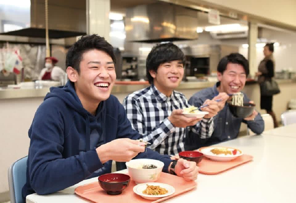 写真:学内の食堂で友達二人と学食を食べるBさん
