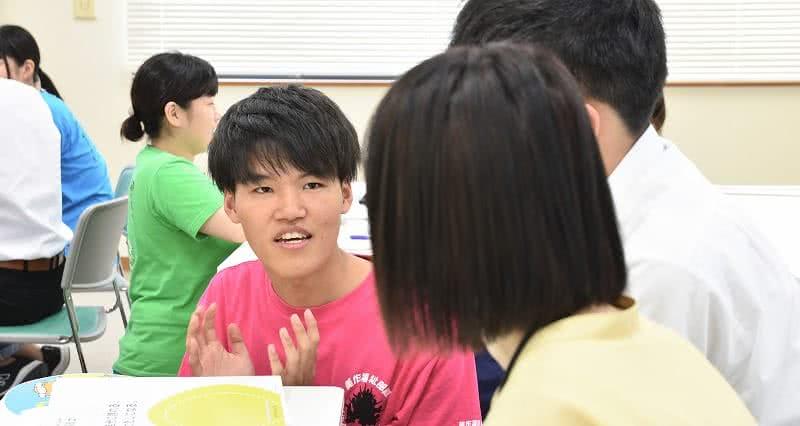写真:二人の高校生に説明を行う男子在学生