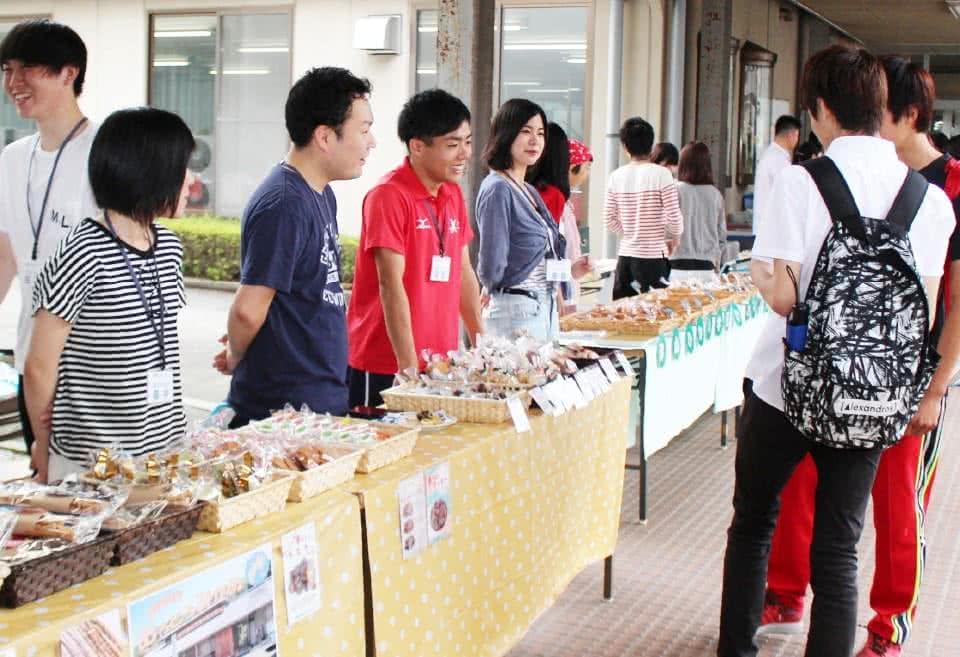 写真:パンやクッキーなどを販売する社会福祉学科の学生と、立ち寄った学生