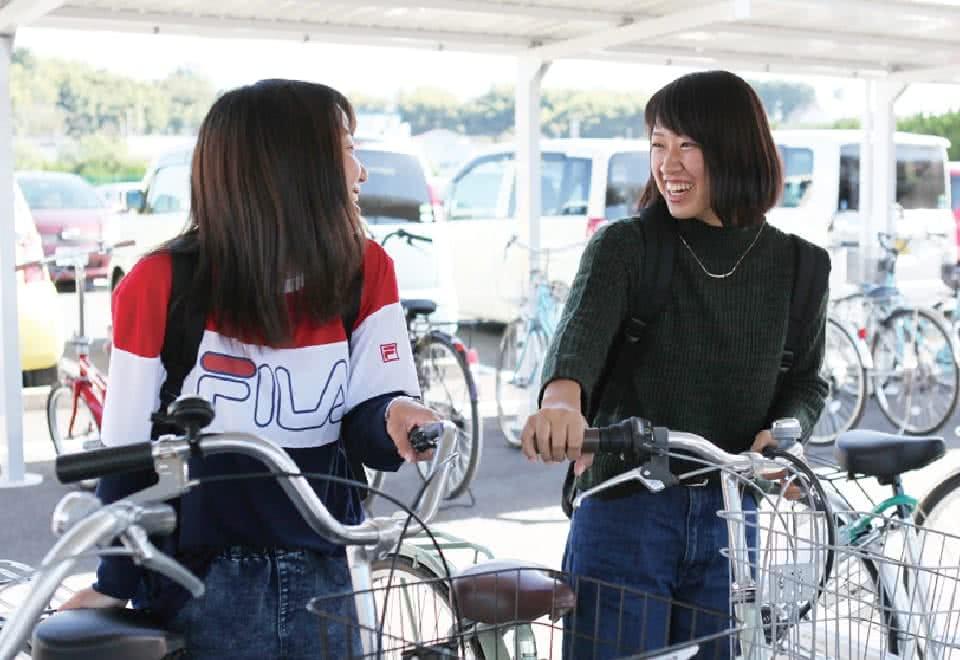 写真:駐輪場で友達を笑い合うAさん