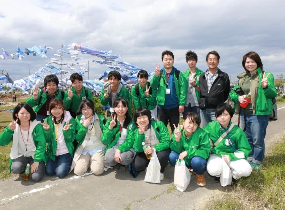 写真:ボランティア活動のメンバーの記念写真。道の上で揃いの緑色の上着を着てピースサインをしている。