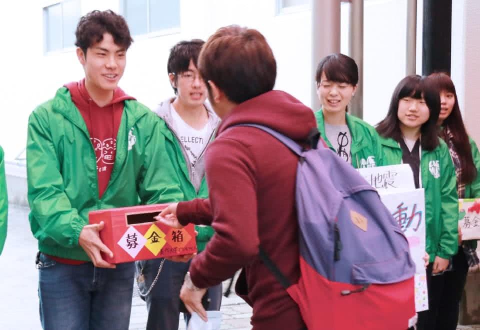 写真:揃いの緑色のジャケットを着て募金活動を行う学生スタッフたち。