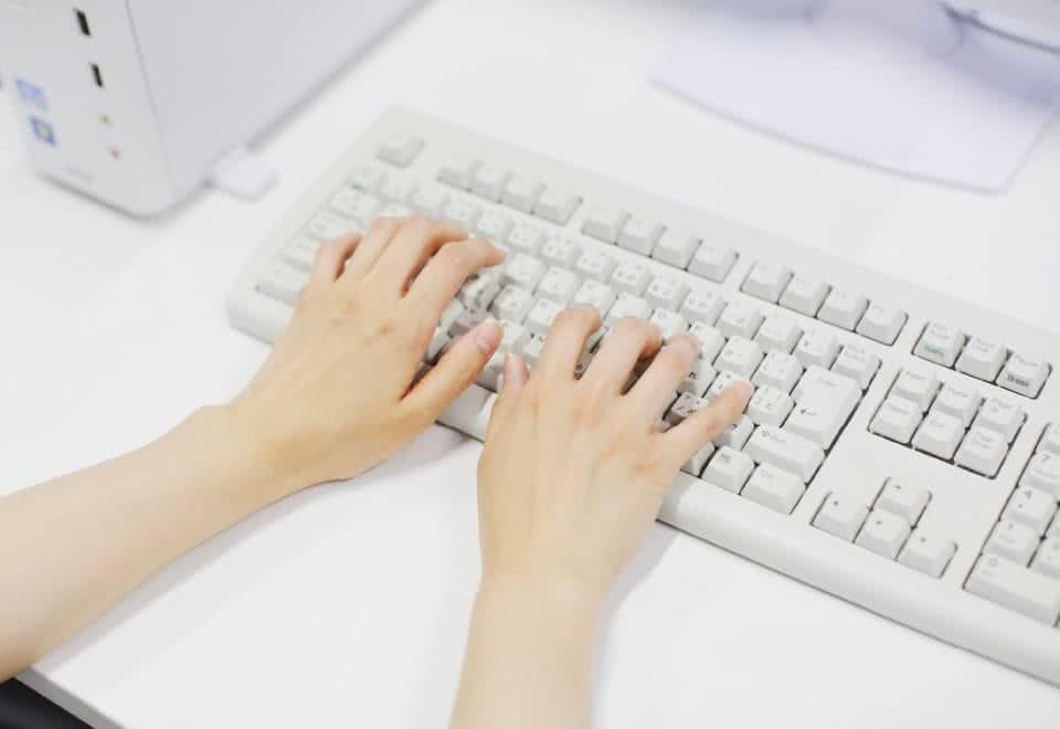 写真:コンピュータのキーボードをタイプする様子