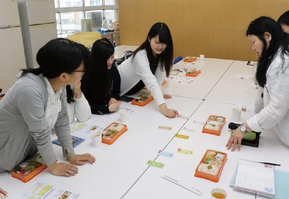 写真:机の上に色々な種類のお弁当を並べて生徒達で話し合いをしている様子