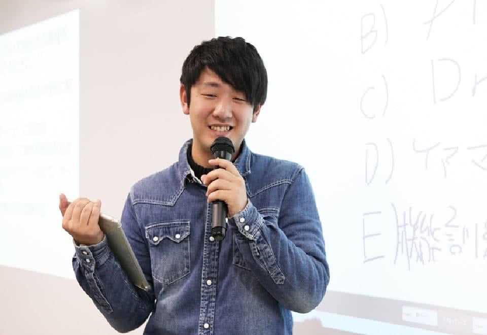 写真:授業にてスクリーンの前に立つCさん
