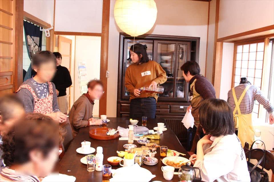 写真:食卓を囲んでご飯を食べながら語り合う学生と、認知症の方とその支援者