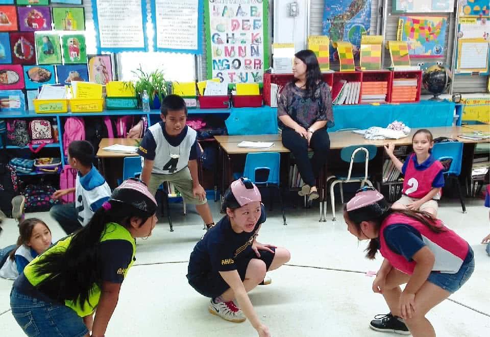写真:グアム文化交流研修。ちょんまげのカツラをかぶりスモウをとっている様子