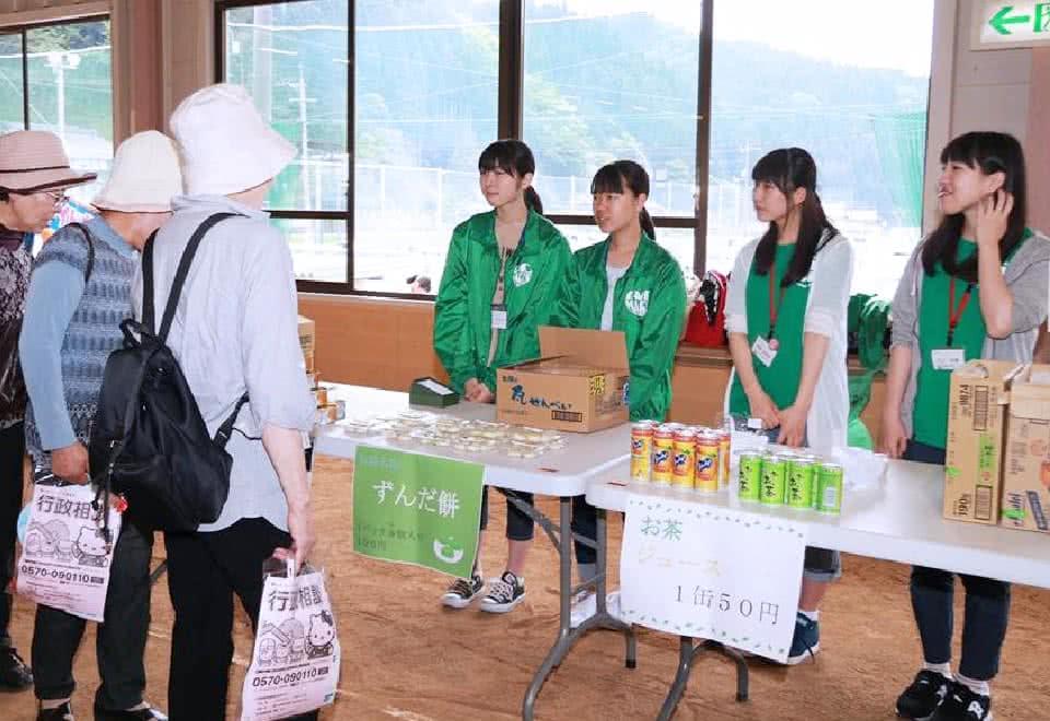 写真:揃いの緑色のジャケットを着て、てずんだ餅やお茶をチャリティマーケットで販売する学生スタッフたち