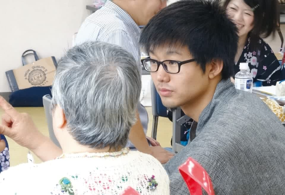 写真:福祉ボランティアでシニアの女性に顔を向ける男子生徒