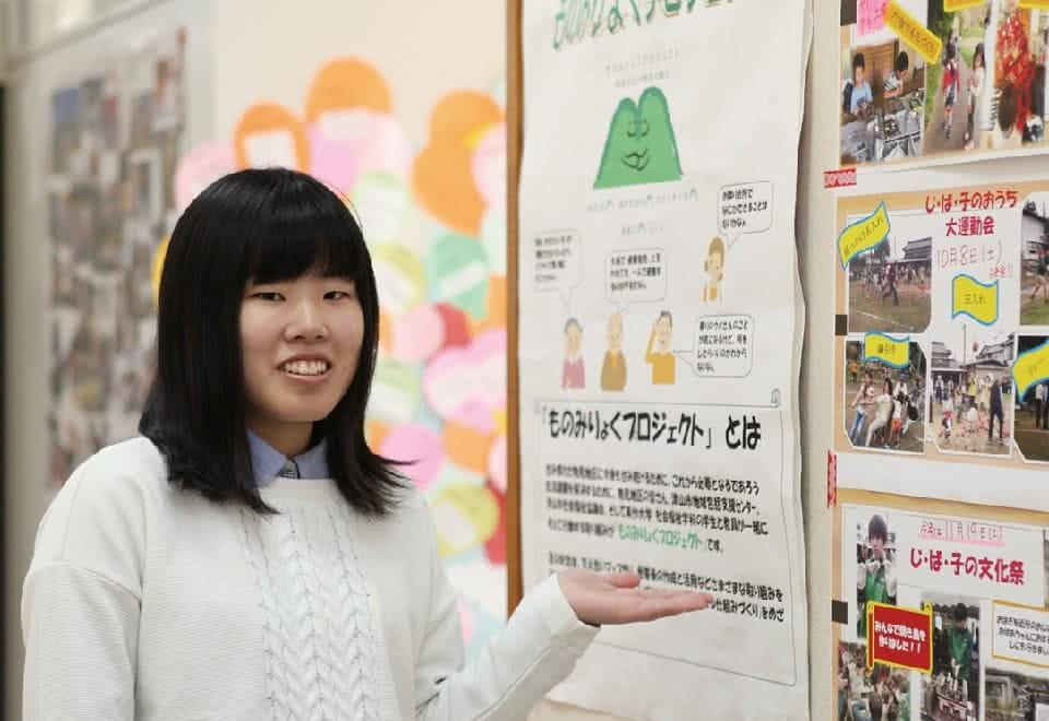 写真:ものみりょくプロジェクトのポスターを案内する女性