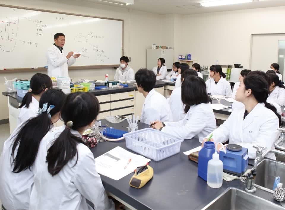 写真:男性教員と生徒たちが実習(講義)を受けている様子。
