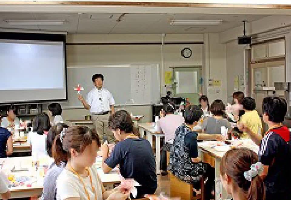 写真:研修会にて手作りおもちゃの作り方を指導する講師と受講する参加者