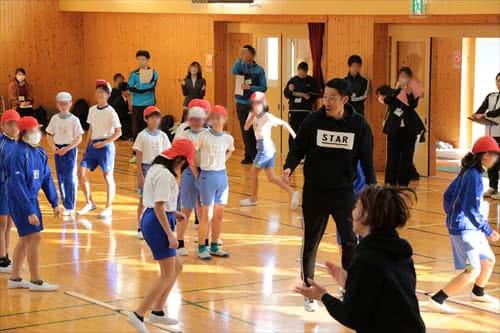 写真:体育館でリズムジャンプの指導をする津田先生
