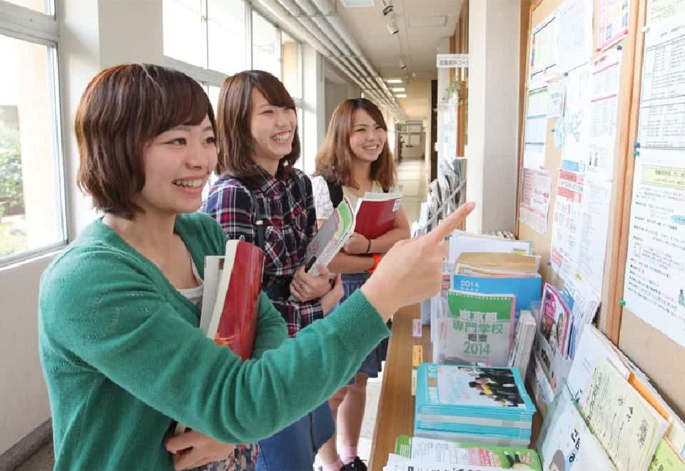 写真:廊下の掲示板に貼られた時間割を見ている3人の女子生徒