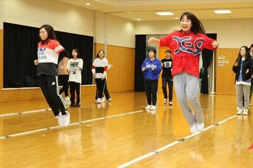 写真:3列に並んで、リズムジャンプに挑戦する大学生
