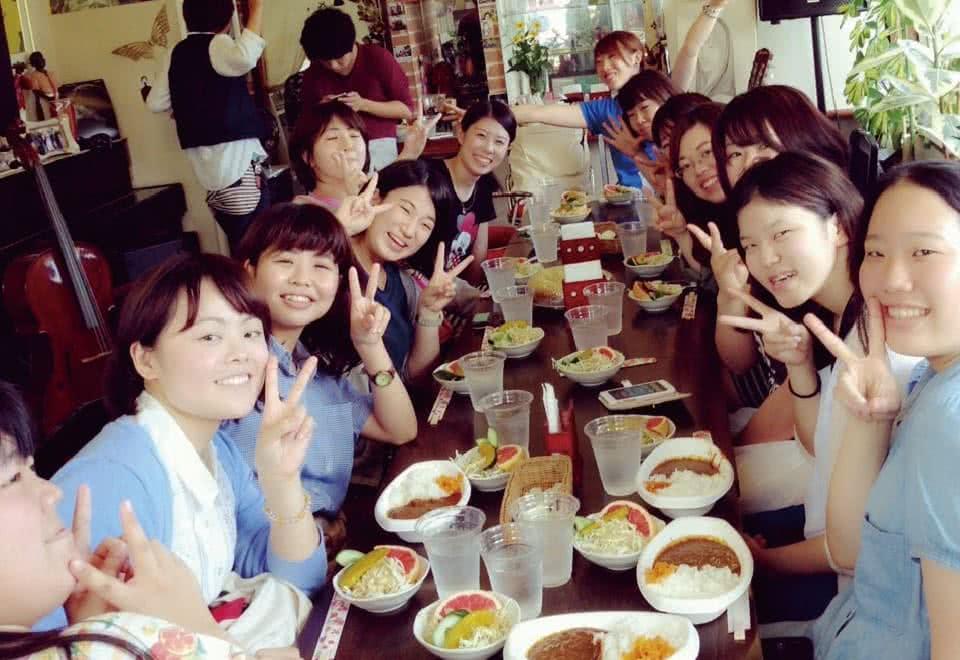 写真:懇親会の様子。テーブルの上にサラダとカレーが並んで、みんな笑顔でピースしています。
