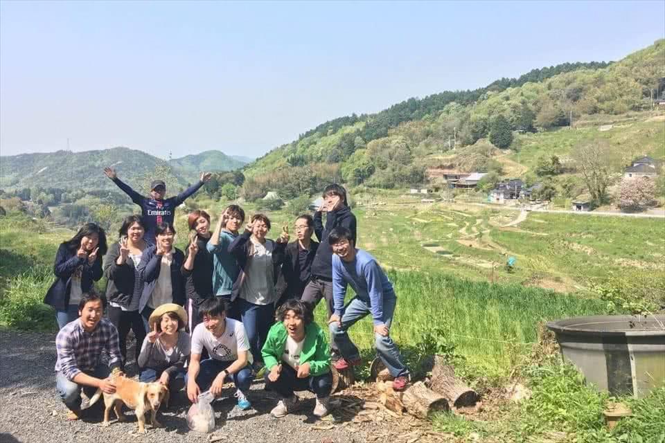 写真:棚田と青空を背景に、学生と教員と地域の方がピースをしている様子