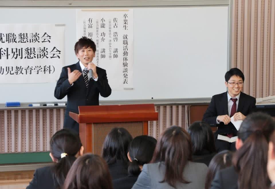 写真:卒業生の講話会の壇上で語る男子卒業生と、それを聞く学生たち