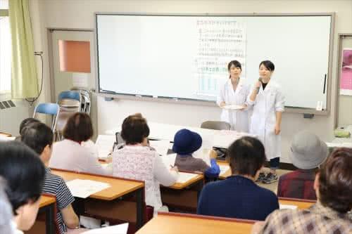 写真:教壇で食品ロスについて話す2名の学生