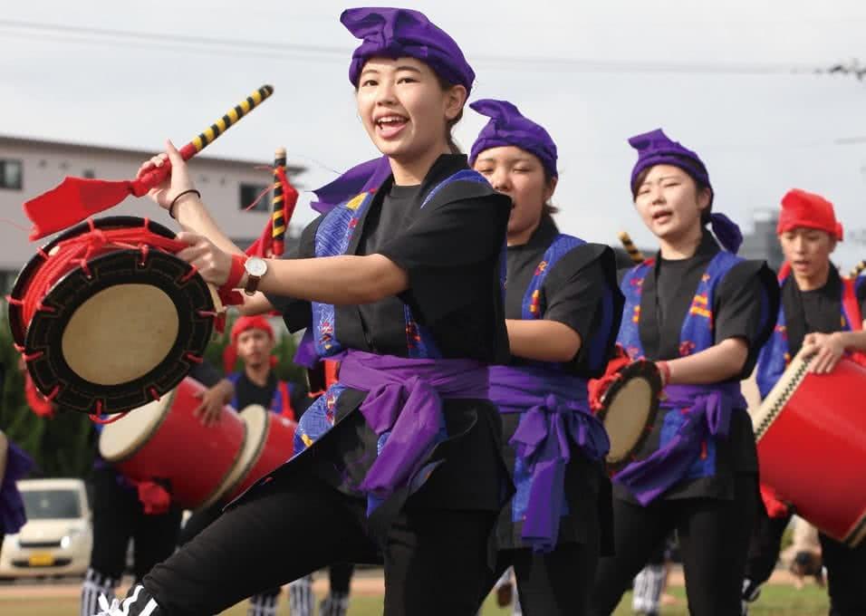 写真:揃いの黒い衣装で和太鼓を手にエイサーを踊る県人会のメンバーたち