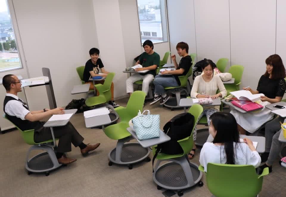 写真:テーブルとキャスタ付きのテーブルチェアーで自由に動きながらグループワークをする学生たち