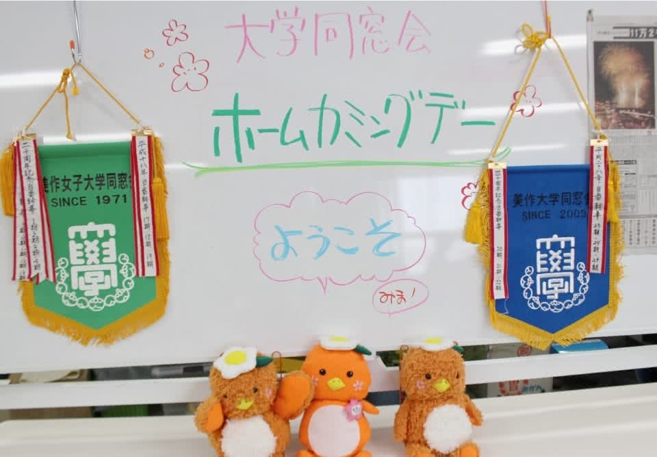 写真:大学同窓会ホームカミングデーようこそと書いたホワイトボードの前に同窓会のフラッグと3体のミマッパちゃんのぬいぐるみ